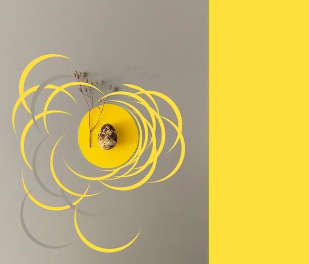 Concetto di pasqua in colori alla moda. uovo di quaglia con fiori secchi su uno sfondo giallo e grigio con spazio di copia.