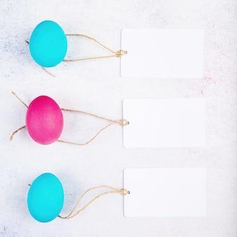Concetto di pasqua. etichette bianche bianche dell'etichetta sulle uova colorate rosa e blu vista dall'alto laici piatta
