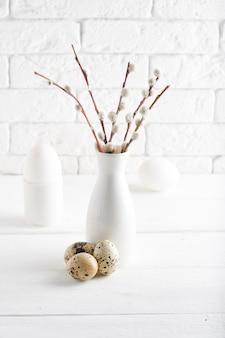 Concetto di pasqua vaso bianco con ramo di salice, uovo bianco, uova di quaglia e tazze su un tavolo bianco copia spazio