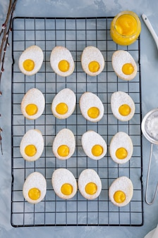 Biscotti pasquali a forma di uovo di pasqua con zucchero a velo e crema al limone