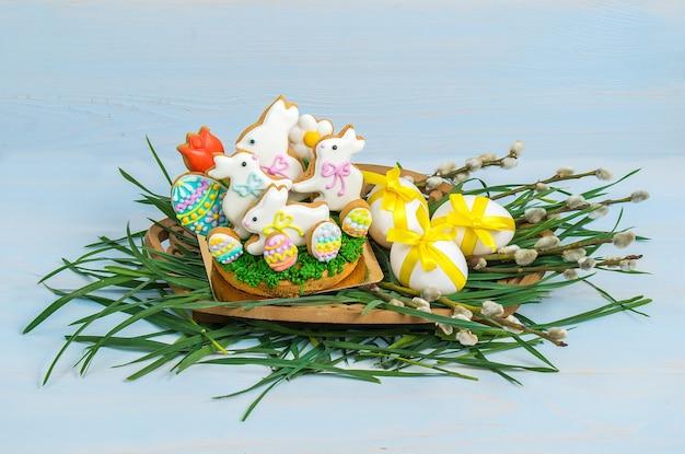 Conigli di biscotti di pasqua e uova decorate con nastro su uno sfondo di legno con erba verde