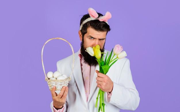 Giorno di pasqua, uomo con bouquet di tulipani con uova di cesto, bel maschio barbuto con orecchie da coniglio.