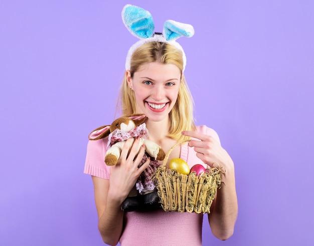 Pasqua. ragazza sorridente in orecchie di coniglio con cesto di uova e coniglietto giocattolo.