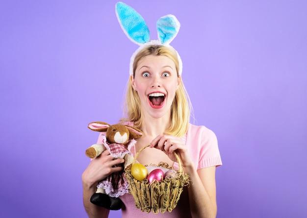 Giorno di pasqua, ragazza sorridente con cesto di uova e coniglietto, donna felice con orecchie di coniglio con peluche.