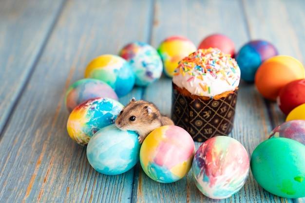 Uova e topo decorati pasquali su fondo di legno turchese. un trattamento tradizionale per le vacanze.