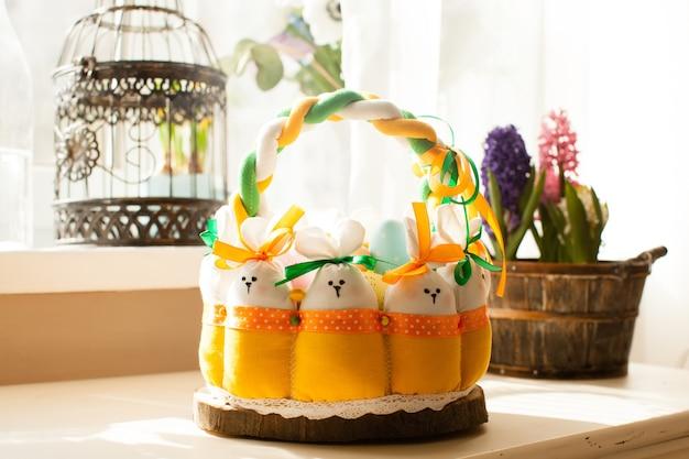 Decorazioni pasquali - cesto in tessuto con conigli e uova, luce mattutina dalla finestra