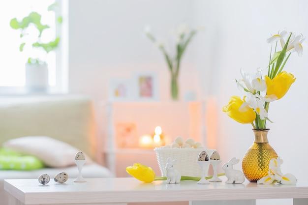 Decorazioni pasquali con fiori primaverili in interni bianchi