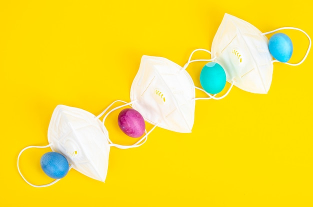 Uova decorative di pasqua e maschere protettive bianche su superficie luminosa