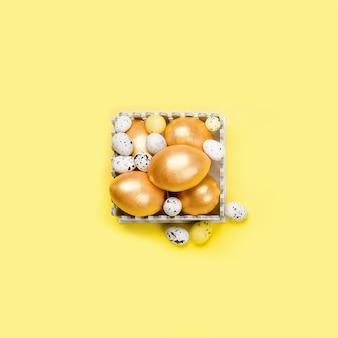 Decorazione pasquale. uova dorate decorative, ramoscelli di salice e tulipani su uno sfondo giallo