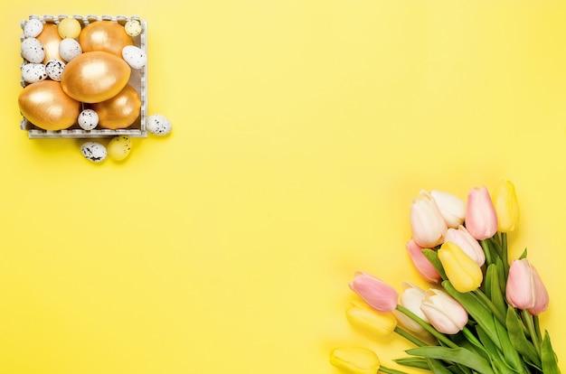 Decorazioni pasquali. uova di pasqua decorative dorate, ramoscelli di salice e tulipani su uno sfondo giallo