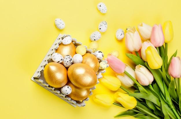 Decorazioni pasquali. uova dorate decorative, ramoscelli di salice e tulipani su sfondo giallo