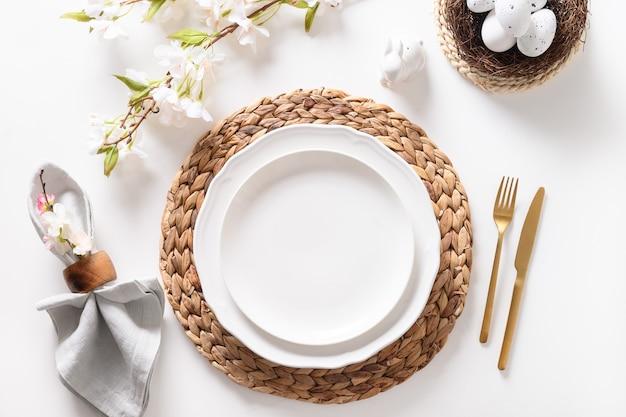 Cena di pasqua con uova, stoviglie festive e tulipani su superficie bianca