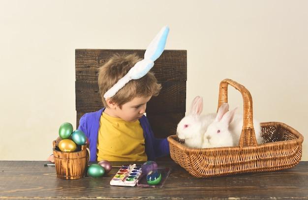 Uovo di pasqua che decora la famiglia felice. bambino con finte orecchie da coniglio.