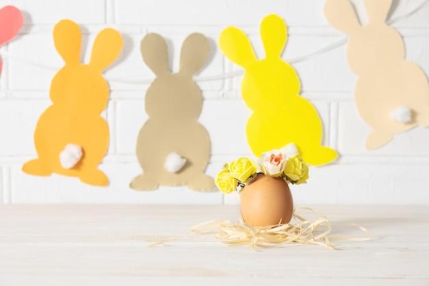 Decorazione dell'uovo di pasqua. uovo di pasqua decorato con ghirlanda di rose gialle e coniglietti di carta.