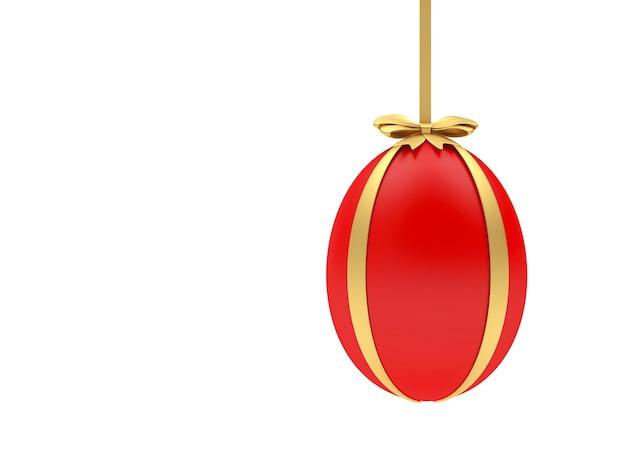 L'uovo di pasqua è appeso a un nastro d'oro con un fiocco