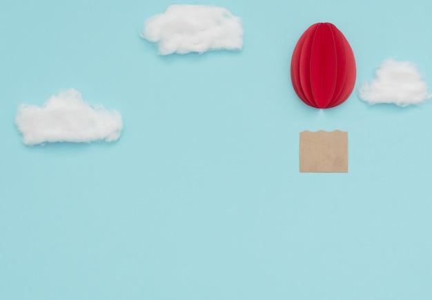 Mongolfiera dell'uovo di pasqua fatta di carta sul cielo blu con nuvole di cotone