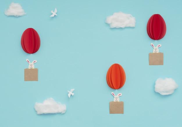 Le mongolfiere di uova di pasqua fatte di carta con coniglietti volano nel cielo azzurro con nuvole di cotone e colombe bianche