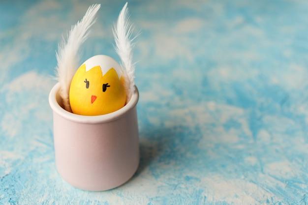 Uovo di pasqua dipinto come pulcino con faccia buffa nella tazza rosa su sfondo blu con texture.