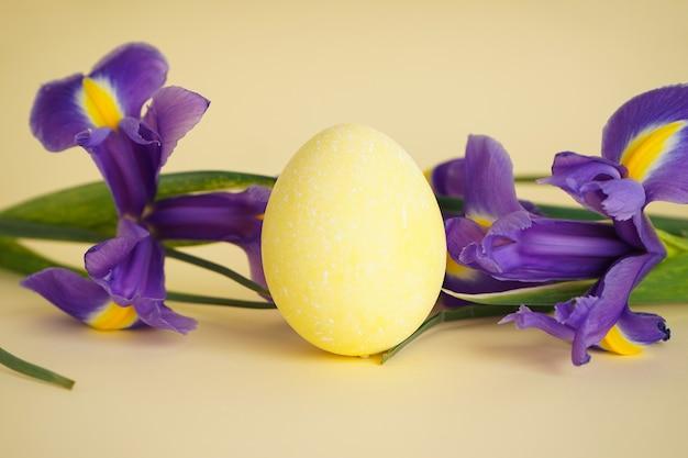 Uovo di pasqua con fiori su sfondo giallo