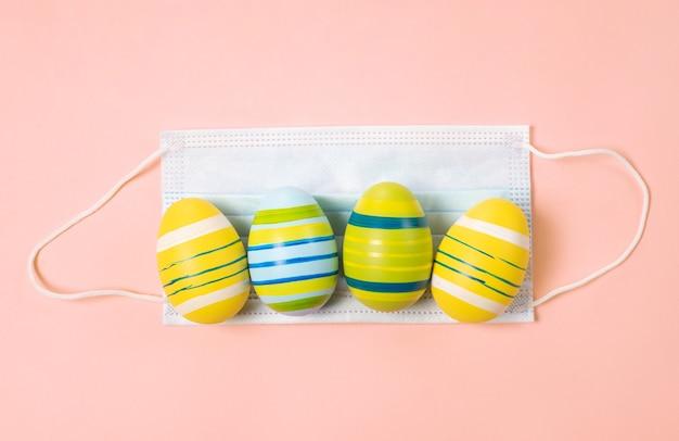 Easter eggs 2021 con coronavirus defense concept (covid19). uova di pasqua su una mascherina medica sul colore rosa pastello.