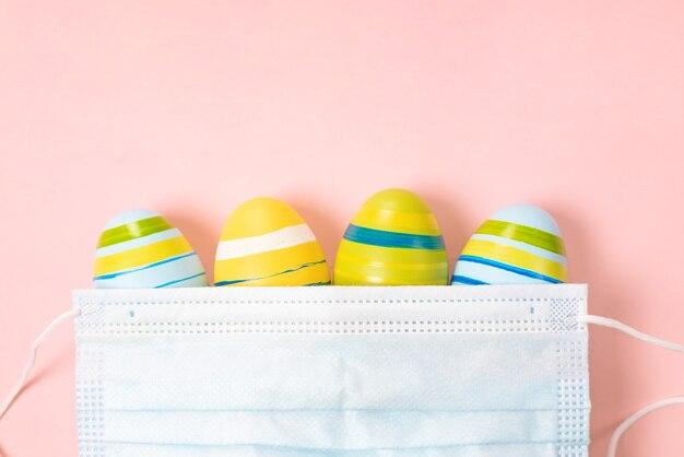 Easter eggs 2021 con coronavirus defense concept (covid19). uova di pasqua sotto una mascherina medica su rosa pastello. protezione antivirus e quarantena.