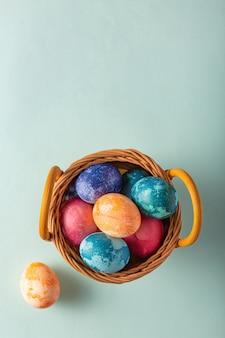 Uova di pasqua in un cesto su sfondo blu