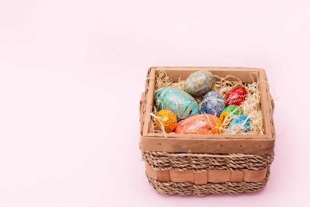 Uova di pasqua nel cestino su sfondo rosa con spazio di copia