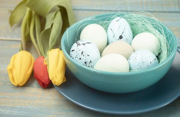 Uova di pasqua nel cestino, piatti, posate e fiori