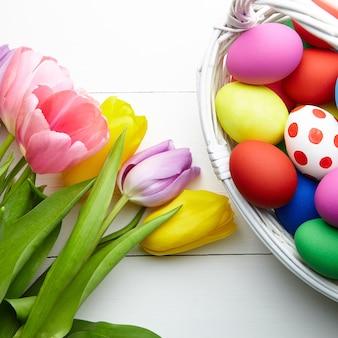 Uova di pasqua nel cestino e fiori colorati di primavera sulla tavola di legno bianco con spazio di copia