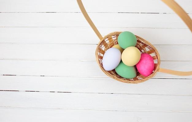 Uova di pasqua in cestino su fondo di legno bianco