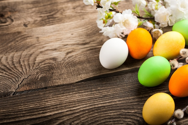 Uova di pasqua, ramoscello di ciliegie e salice sul tavolo di legno