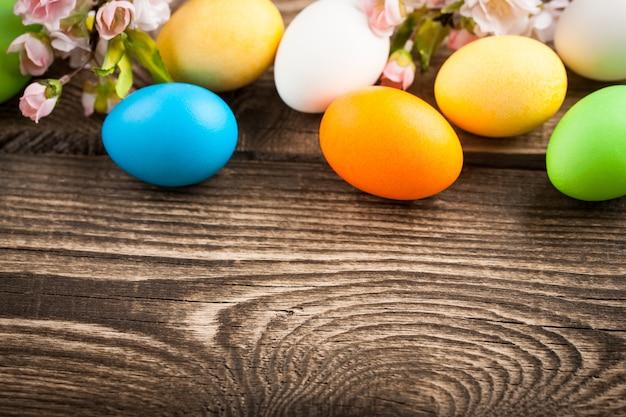 Uova di pasqua, ramoscelli di ciliegie sul tavolo di legno