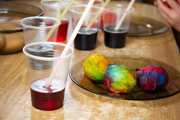 Uova di pasqua e vernici liquide colorate sul tavolo