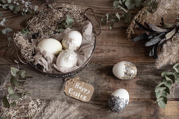 Uova di pasqua in un cesto decorativo con fiori secchi su un tavolo di legno. felice pasqua concetto.