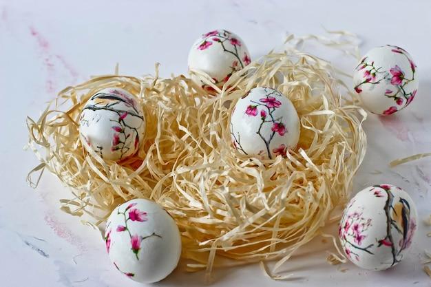 Uova di pasqua in un nido decorativo su uno sfondo di marmo