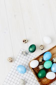 Le uova di pasqua di diversi colori si trovano su un tavolo in legno copy space e