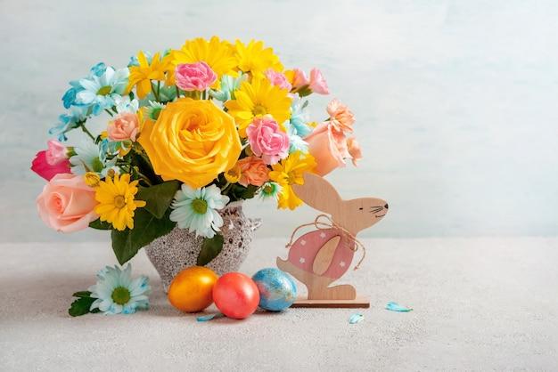 Uova di pasqua, coniglio di pasqua e fiori primaverili, spazio per il testo. buona pasqua. sfondo di pasqua di congratulazioni.