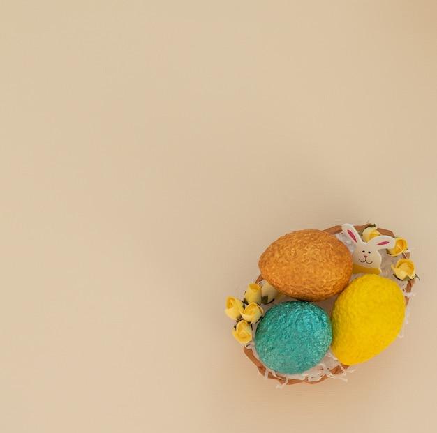 Uova di pasqua nel cestino delle uova con carta bianca come un nido e fiori primaverili gialli su beige
