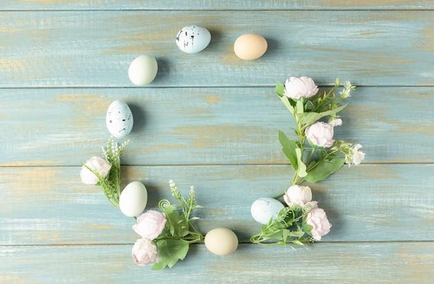 Uova di pasqua e fiori su uno sfondo di legno blu rustico