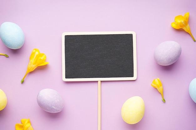 Uova di pasqua e fiori di fresia su una superficie viola. disposizione piatta.
