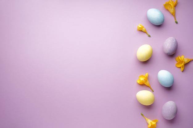 Uova di pasqua e fiori di fresia su viola