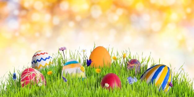 Uova di pasqua in erba verde con fiori, sfondo di buone feste