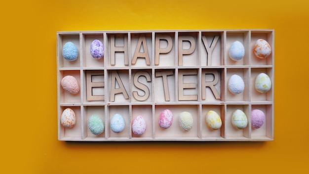 Uova di pasqua. testo di buona pasqua. priorità bassa arancione della decorazione di feste. elementi di arredo in contenitori di legno