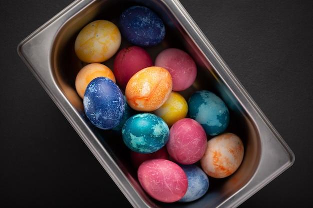 Uova di pasqua in un contenitore di metallo si chiudono su un nero