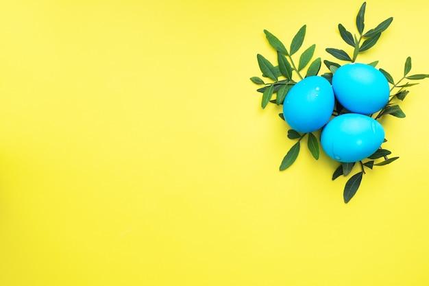 Uova di pasqua dipinte a mano colorate su un tavolo giallo