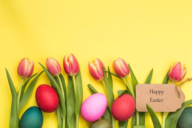 Uova di pasqua dipinte e tulipani con sfondo giallo e testo felice pasqua aprile concetto