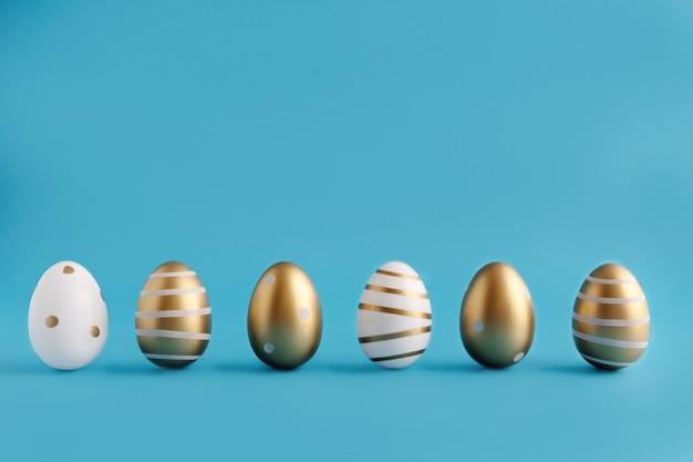 Le uova di pasqua dipinte con vernice dorata in diversi modelli stanno in fila su uno sfondo blu. posto per il testo. concetto di pasqua. elemento di design.