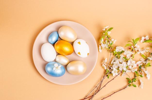 Uova di pasqua su un piatto su una superficie beige con spazio di copia
