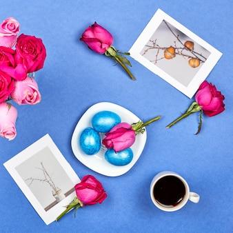 Uova di pasqua, rose rosse, una tazza di caffè nero e immagini di pasqua su sfondo blu
