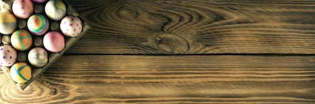 Uova di pasqua su un supporto su una superficie di legno con posto per testo, vista dall'alto, banner